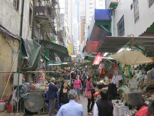 Various vendors and stalls selling their wares at a local street market as the ever-present skyscrapers loom ominousliy in the background