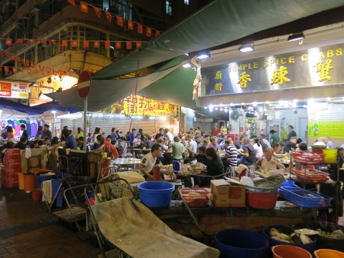 Diners enjoying the festive atmosphere and tasty treats near a street market in Kowloon