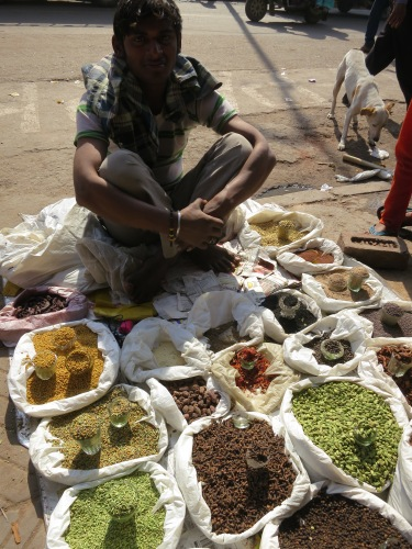 A spice vendor setting up shop right on the sidewalk