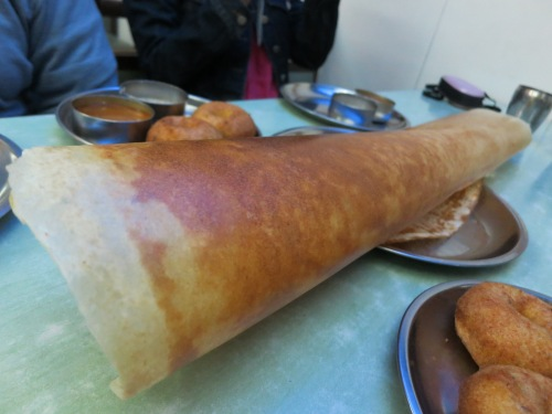 Dosa, a thin, pancake/crepe-like creation made from a batter of rice flower and lentils that can be stuffed with a variety of fillings.  To eat these behemoths (and this isn't even the biggest one available), simply crack off a few shards of the crispy exterior and use them to scoop up the stuffing