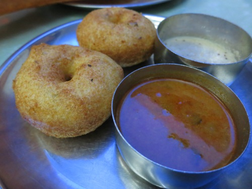 Lentil Doughnuts known as Vada served with a spicy sambar soup and a coconut chutney