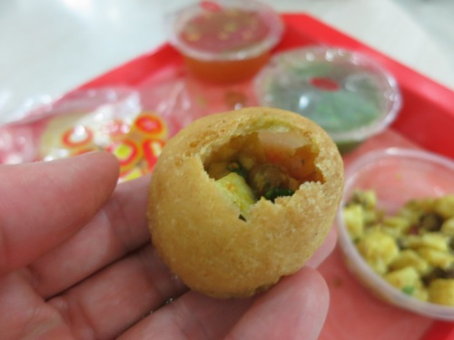 Gol Gappas, sometimes known as pani puri, which consists of small hollow shells of deep-fried dough into which you then stuff a variety of fillings and top off with a sweet-sour liquid before downing the whole thing in one bite