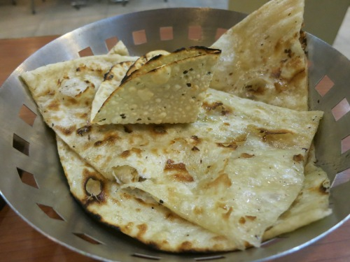 A basket of Naan bread, a leavened flat bread cooked in an oven and often served in a tear-drop shape.  Diners then tear off small pieces of the bread and use them to pick up (or scoop up) the various curries or masalas