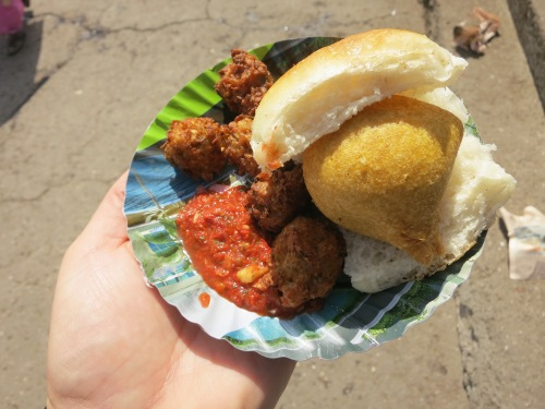 "Vada Pau (sometime written Vada Pao) -- joking known as an ""Indian Burger,"" this staple of Bombay street food features a small potato pattie sandwiched in a slider bun.  In this iteration, it is also served with a few fried treats and a generous splash of chile sauce"