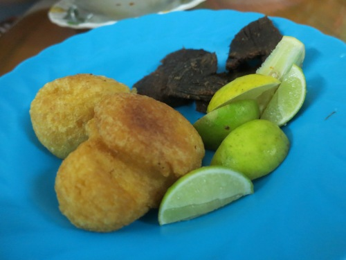 Various Chin snacks, such as dried beef jerky, doughy bean puffs, and a handful of limes