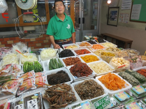 A friendly vendors offering up samples of his salted, pickled, fermented, and just generally preserved foods