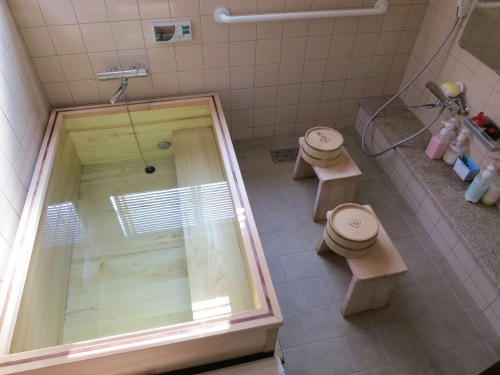 An example of a Japanese style bath (I particularly like the matching cedar wood tub, stools, and buckets).  The proper etiquette is to use the stool, bucket, and facet to first wash yourself off thoroughly.  Once you've rinsed off all of the soap, you can then move to the tub to soak for a while.  Although in this example, the bath is only meant for one at a time, the bath water will still be left untouched (thus the no soap in the tub rule), as it will be used by anyone else looking to soak in the tub that night.  This may seem odd to Westerners at first, but just think of it like you would a hot tub or Jacuzzi – and of course they change the water each day.