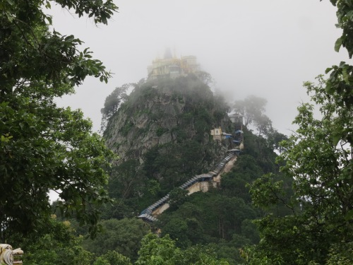 The first peak through the clouds at the gilded temple atop Mount Popa