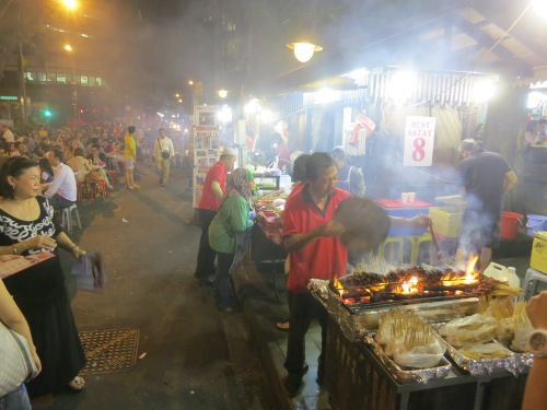 The smoky haze created by a line of Satay vendors all delicately fanning their flames